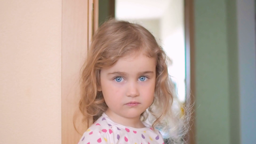 videoblocks-little-girl-is-blonde-with-blue-eyes-stands-near-the-wall-in-the-house-child-with-regret-looking-at-the-cameraportrait-of-a-sad-girl_hbzn27pal_thumbnail-full01